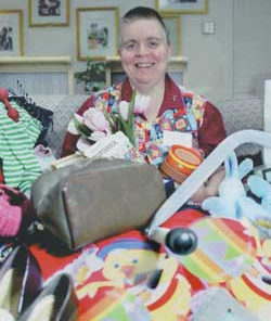 Beth Johnson sits among a mountain of items she persuaded people to discard at one of her de-clutter workshops.